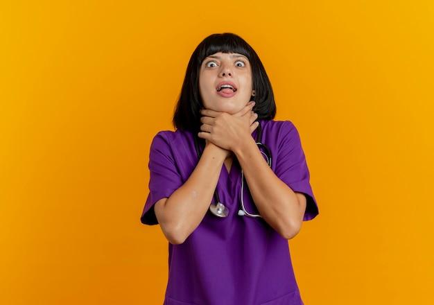 Medico femminile giovane brunetta divertente in uniforme con lo stetoscopio che si soffoca