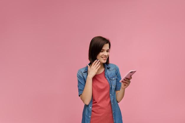 Смешная молодая брюнетка женщина держит розовый смартфон и улыбается