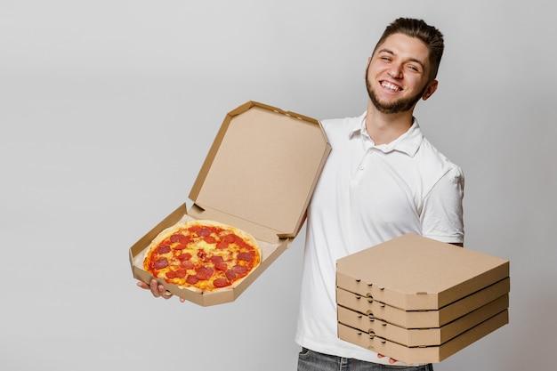 Забавный молодой кавказский курьер с пиццей и 4 картонными коробками с пиццами