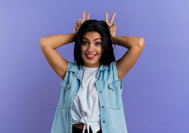 Divertente giovane ragazza caucasica tira fuori la lingua e mette le mani sulla testa gesticolando corna isolato su sfondo viola con spazio di copia