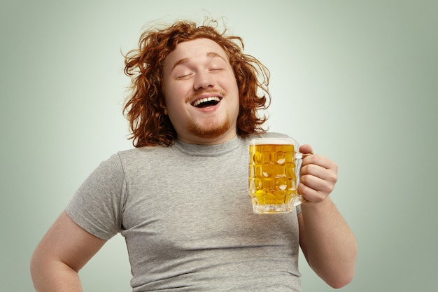 Забавный молодой мужчина кавказской, чувствуя себя счастливым и расслабленным, ожидая свежего холодного пива в руках после тяжелого рабочего дня, закрывая глаза от удовольствия. бородатый мужчина с избыточным весом пьет пиво