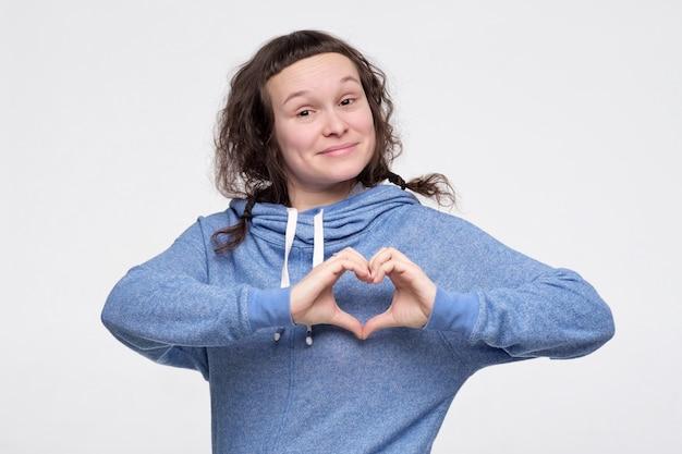 Смешной молодой кавказский человек показывая знак сердца.