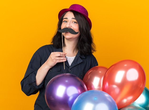Funny young caucasian party girl wearing party hat holding bunch of balloons behind back and fake mustache on stick above lips isolated on orange wall