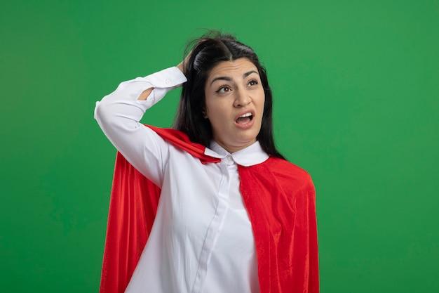 Divertente giovane ragazza caucasica del supereroe grattandosi la nuca alla ricerca di un'idea con la bocca aperta guardando l'angolo isolato sulla parete verde con lo spazio della copia