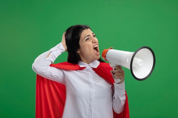 Divertente giovane ragazza caucasica del supereroe che grida in altoparlante e che tiene la testa guardando l'angolo isolato sulla parete verde