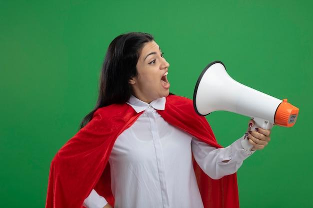 Divertente giovane ragazza caucasica del supereroe in piedi nella vista di profilo che parla in altoparlante e divertirsi guardando dritto isolato sulla parete verde