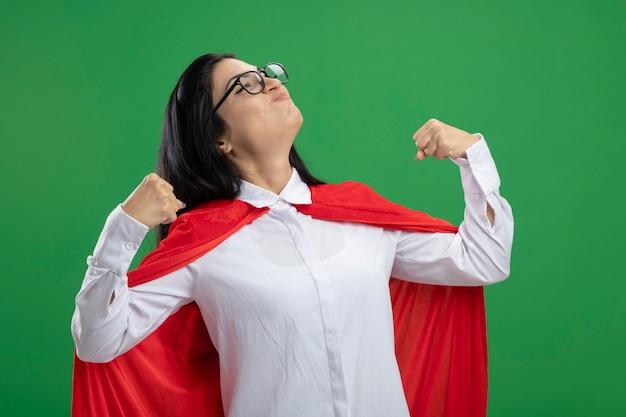 Divertente giovane ragazza caucasica del supereroe con gli occhiali che flette i suoi muscoli e si diverte con gli occhi chiusi isolati sulla parete verde con lo spazio della copia