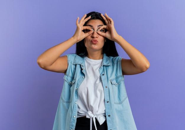 Divertente giovane donna caucasica guarda attraverso le dita isolate su sfondo viola con spazio di copia