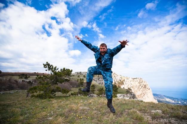 Забавный молодой веселый кавказский человек прыгает на холмы с зеленой травой на фоне голубого неба и белых облаков. концепция долгожданного путешествия и туризма