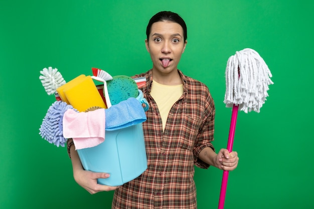Funny young cleaning woman in plaid shirt holding bucket with cleaning tools looking at front sticking out tongue standing over green wall