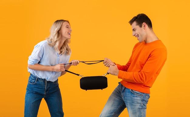 Divertente giovane coppia in lotta per un altoparlante wireless che ascolta musica in stile colorato isolato su giallo