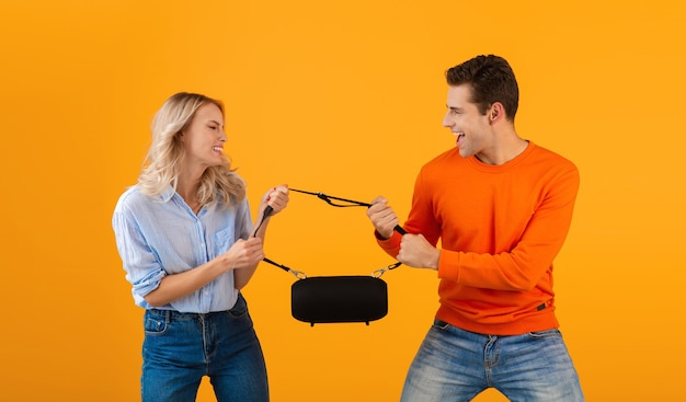 Funny young couple fighting for wireless speaker listening to music colorful style