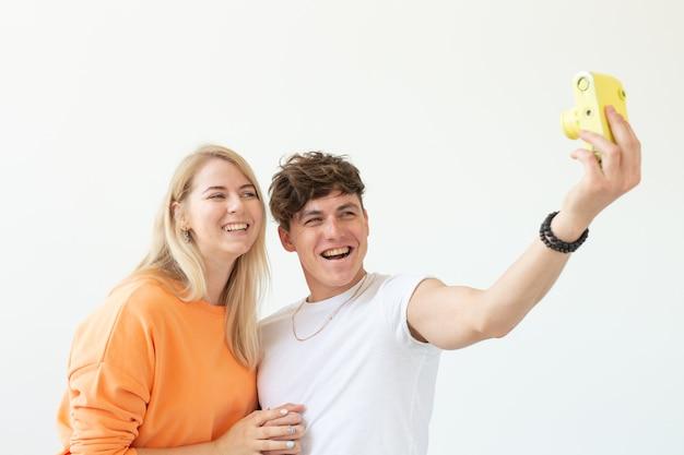 사랑 귀여운 남자와 흰 벽에 포즈 빈티지 노란색 필름 카메라에 selfie를 만드는 매력적인 여자에 재미있는 젊은 부부. 사진과 취미의 개념 애호가.
