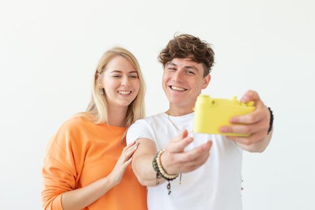 Смешная молодая влюбленная пара, милый мужчина и очаровательная женщина, делающие селфи на винтажной желтой пленочной камере