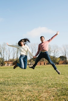 Funny young couple jumping on field holding hands