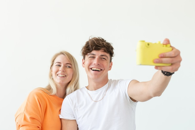 Funny young couple in love cute man and charming woman making selfie on vintage yellow film camera