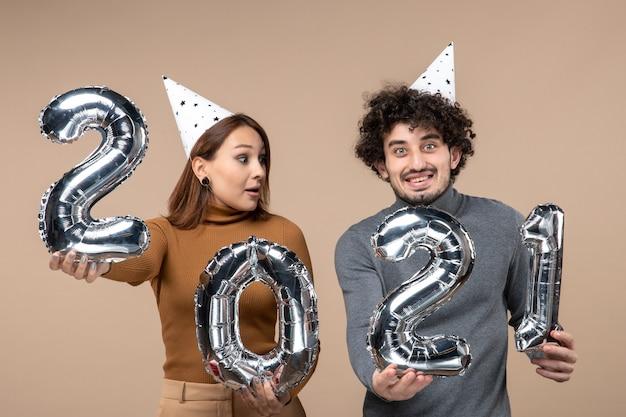面白い若いカップルは、カメラの女の子のショーと灰色の男と新年の帽子のポーズを着ています