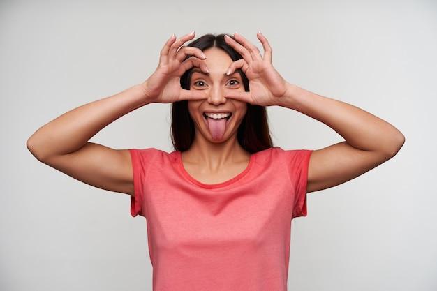 Divertente giovane donna dai capelli scura gioiosa in t-shirt rosa occhiali pieghevoli dalle mani alzate mentre guarda allegramente e mostra la sua lingua, isolata