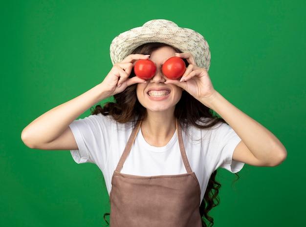 원예 모자를 쓰고 제복을 입은 재미 젊은 여성 정원사는 복사 공간이 녹색 벽에 고립 된 눈 앞에서 토마토를 보유하고 있습니다.