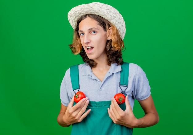新鮮なトマトを保持しているジャンプスーツと帽子を身に着けている面白い若い庭師の男