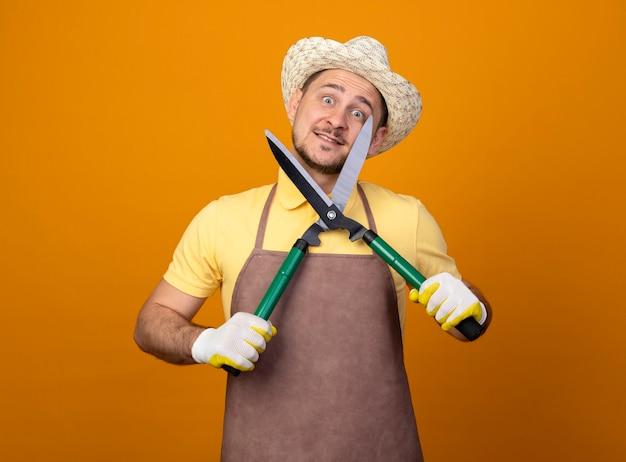 점프 슈트와 모자를 쓰고 재미있는 젊은 정원사 오렌지 벽 위에 서있는 행복한 얼굴로 웃는 전면을보고 울타리 가위를 들고 모자