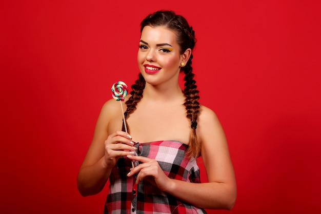 Funny young girl holding a lollipop and posing for kamerñ‹ over red wall, red wall, pigtails