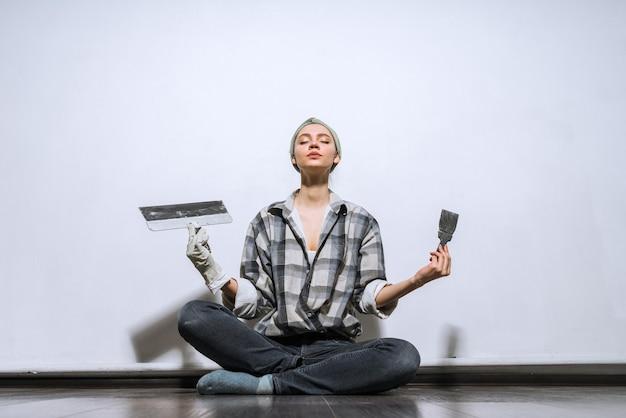 Забавная молодая девушка в клетчатой рубашке сидит на полу, держит в руках шпатели, делает ремонт