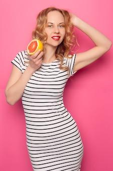 분홍색 파스텔 배경에 분리된 신선한 익은 자몽 오렌지 과일 반으로 눈을 덮고 있는 여름 옷을 입은 재미있는 어린 소녀. 사람들의 생생한 생활 방식은 휴가 개념을 완화합니다. 모의 복사 공간