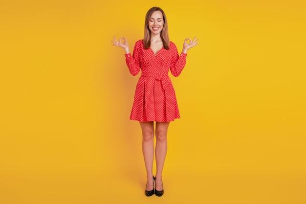 노란색 배경에 고립 된 명상 포즈를 취하는 재미 있는 어린 소녀