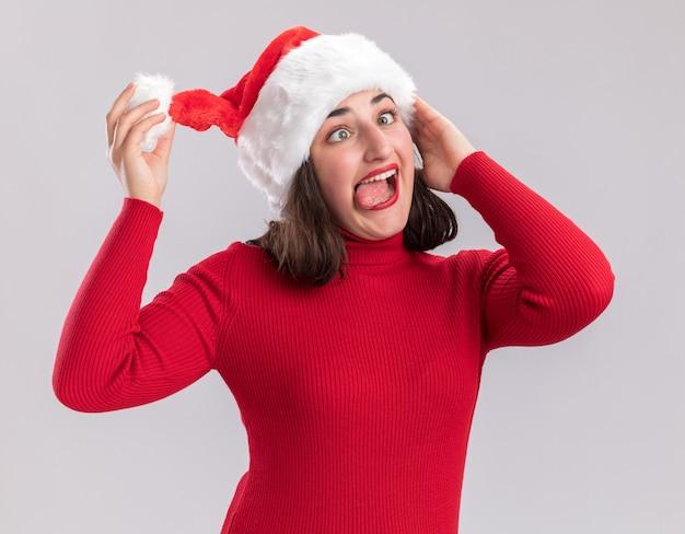 Ragazza divertente in maglione rosso e cappello della santa che fa smorfia che attacca fuori linguetta che sta sopra il muro bianco