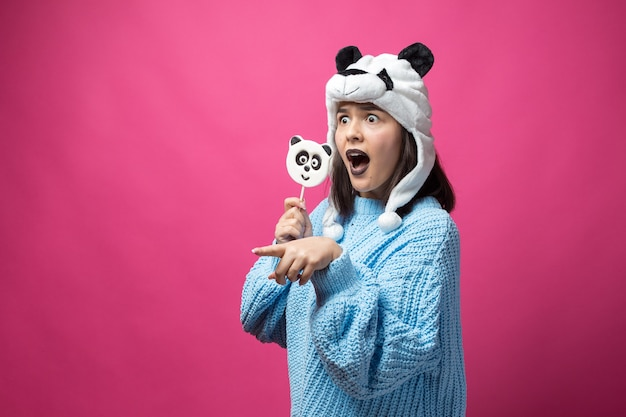 맛있는 판다 롤리팝을 손에 들고 머리에 모자를 쓰고 분홍색 배경에 서 있는 재미있는 어린 소녀.