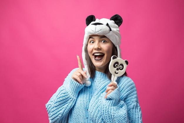 손에 맛있는 판달롤리팝을 들고 머리에 모자를 쓰고 서 있는 재미있는 어린 소녀