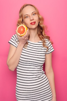 Funny young girl in summer clothes covering eyes with halfs of fresh ripe grapefruit orange fruit isolated on pink pastel background. people vivid lifestyle relax vacation concept. mock up copy space