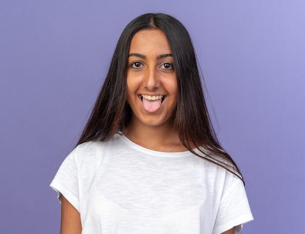 Ragazza divertente in maglietta bianca che guarda l'obbiettivo con la faccia felice che tira fuori la lingua in piedi su sfondo blu