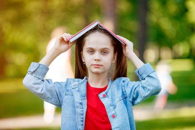 Смешная молодая девушка с книгой над головой