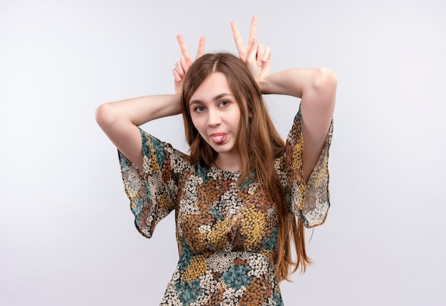 Divertente ragazza giovane con i capelli lunghi che indossa abiti colorati che mostra segni di vittoria sopra la sua testa spuntavano lingua
