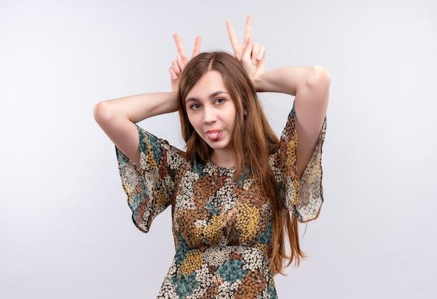 カラフルなドレスを着て長い髪の面白い若い女の子は、舌を突き出して彼女の頭の上に勝利の兆候を示しています