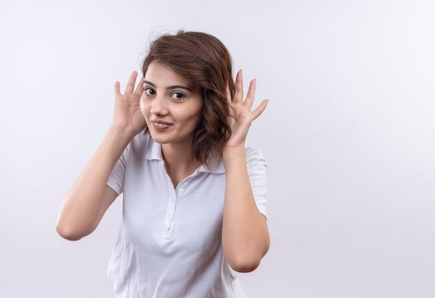 손바닥으로 큰 귀를 유쾌하게 모방하는 흰색 폴로 셔츠를 입고 짧은 머리를 가진 재미있는 어린 소녀