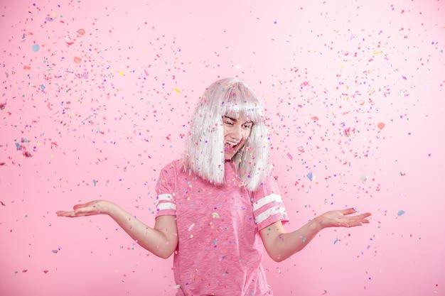 Divertente ragazza con i capelli d'argento dà un sorriso e un'emozione su sfondo rosa con coriandoli.