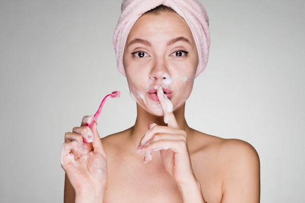 A funny young girl with a towel on her head put a finger to her lips, shaves her face like a man