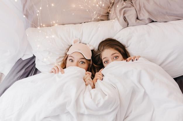 Ragazze giovani divertenti che si nascondono sotto la coperta. foto interna di sorelle emotive che si divertono durante il servizio fotografico mattutino.