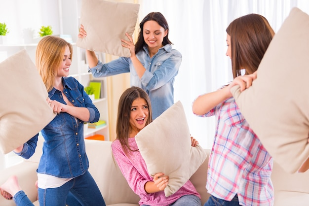 Funny young girls pillow fight on the sofa.