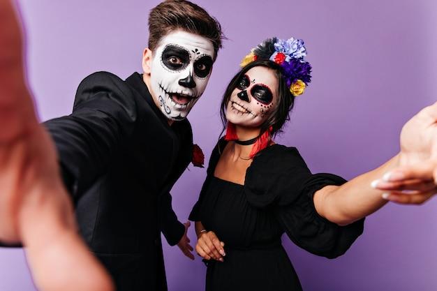 재미있는 젊은 남자와 그의 여자 친구는 얼굴에 미소를 지으며 셀카를 만듭니다. 보라색 스튜디오에서 할로윈 화장과 장난 꾸 러 기 부부의 초상화.
