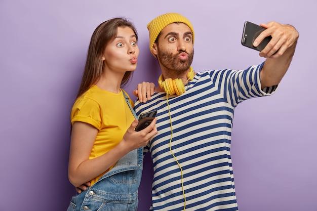 Забавный молодой парень и женщина делают гримасу, держат губы округлыми, фотографируют на переднюю камеру современного мобильного телефона, делают селфи-фото