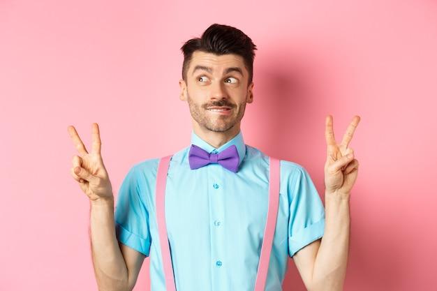 Забавный молодой парень в галстуке-бабочке развлекает людей на праздничном мероприятии, демонстрирует знаки мира и возбужденно смотрит в сторону, стоя над розовым.