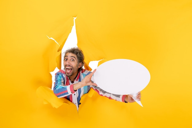 黄色い紙の引き裂かれた穴に空きスペースのある白いページを指している面白い若い男
