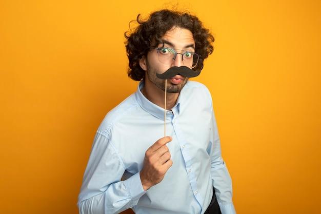 Забавный молодой красивый кавказский мужчина в очках держит поддельные усы на палочке над губами, глядя в камеру, делая жест поцелуя, изолированный на оранжевом фоне с копией пространства