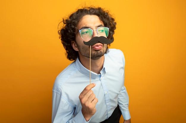 Divertente giovane uomo bello con gli occhiali mantenendo baffi finti sul bastone sopra le labbra guardando il lato facendo gesto di bacio isolato sulla parete arancione