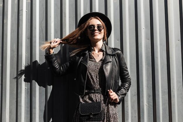 Смешная молодая счастливая девушка с волосами в модной повседневной одежде с кожаной курткой, платьем, шляпой и солнцезащитными очками стоит возле металлического фона в солнечный день