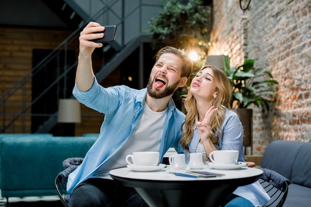 Funny young loving couple making selfie photo on the smartphone together while sitting in cafe or hotel and having coffee